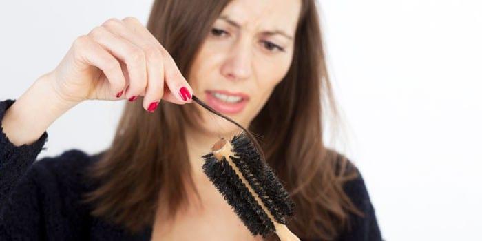 Женщина снимает выпавшие волосы с расчески
