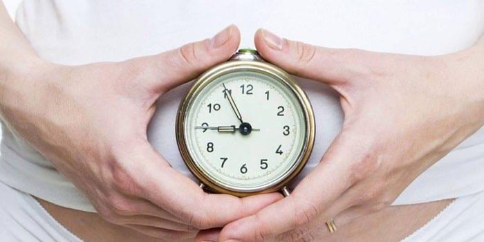 Девушка держит часы в руках
