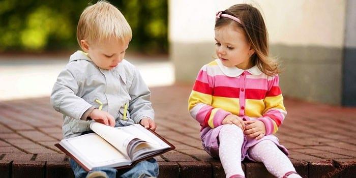 Мальчик и девочка листают книгу