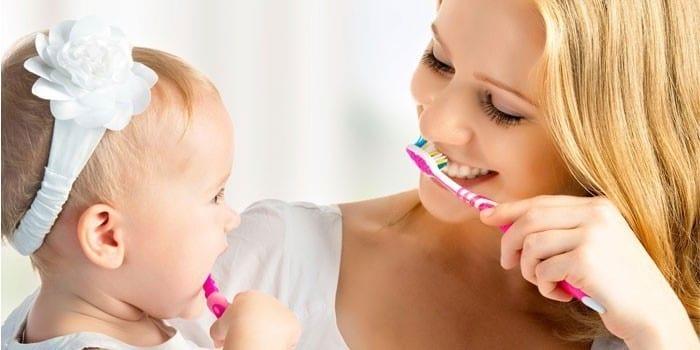Мама вместе в дочкой чистят зубы