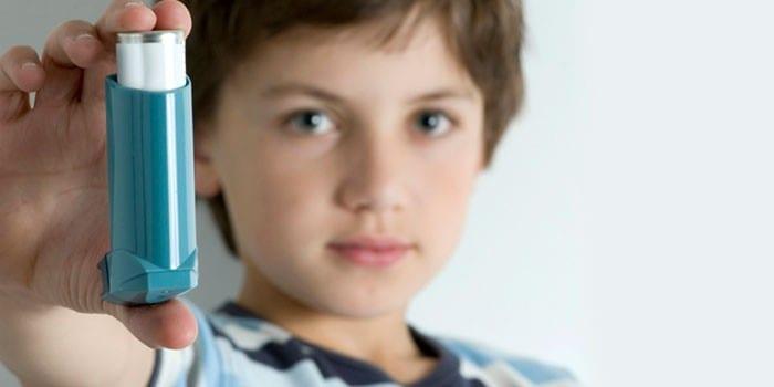 Мальчик держит в руке ингалятор