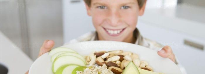 Подросток держит тарелку с фруктами и орехами