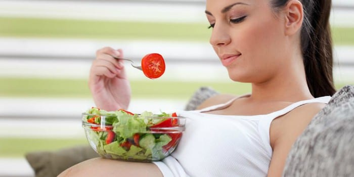 Беременная девушка есть овощной салат