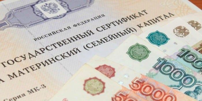 Сертификат на материнский капитал и денежные купюры