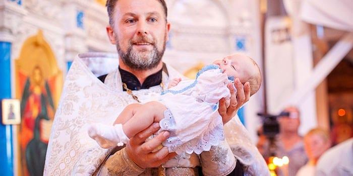 Священник с ребенком на руках