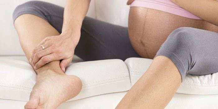 Беременная девушка массирует себе ногу