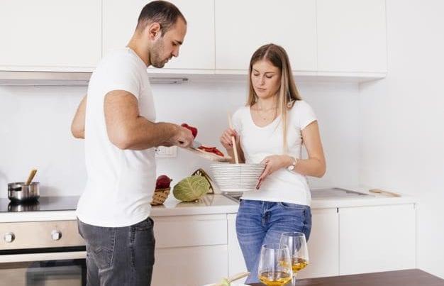 Супруги готовят на кухне
