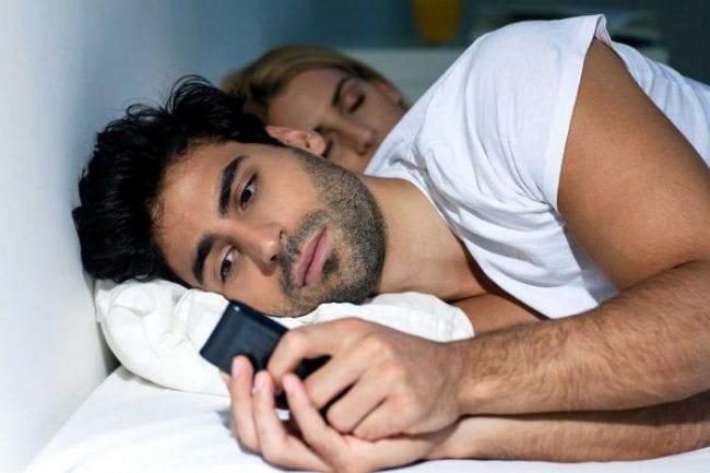 Мужчина с телефоном и спящая жена