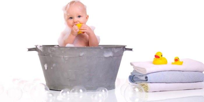 Малыш купается в тазу