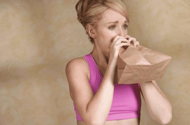Девушка дышит в бумажный пакет