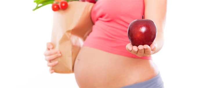 Беременная женщина с продуктами и яблоком