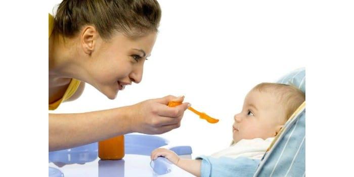 Мама кормит из ложечки малыша