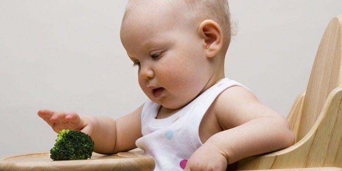 Ребенок сидит на стульчике и играет с брокколи