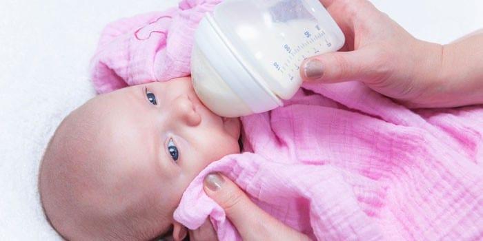 Грудного ребенка кормят из бутылочке
