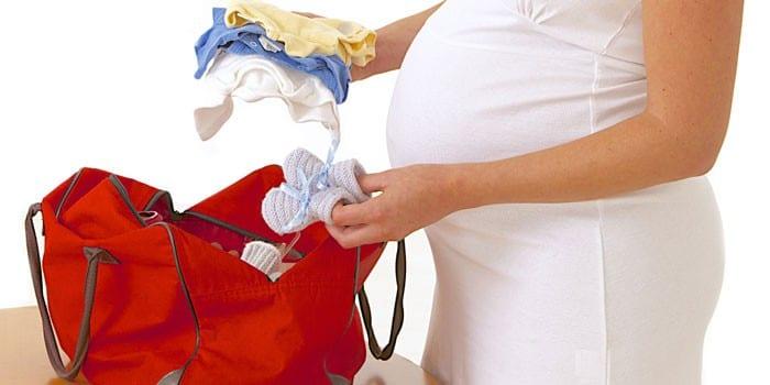 Беременная девушка собирает вещи