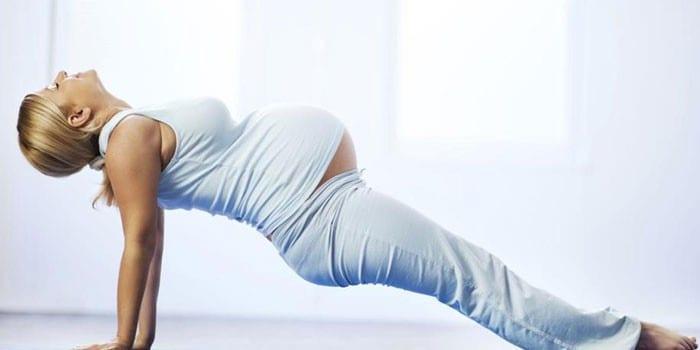 Беременная девушка делает гимнастику