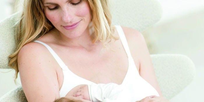 Женщина в бюстгалтере кормит ребенка