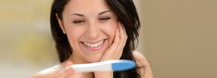 Девушка радуется тесту на беременность