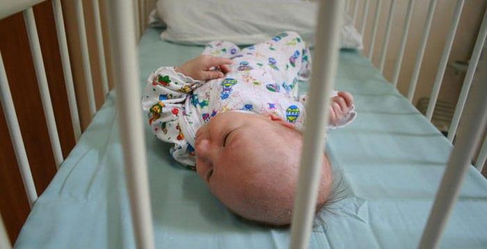 Новорожденный ребенок в кроватке