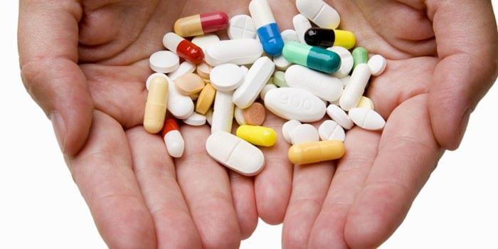 Таблетки и капсулы на ладонях