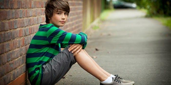 Мальчик сидит у стены
