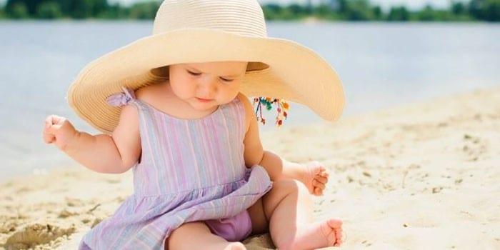 Девочка в шляпе сидит на песке