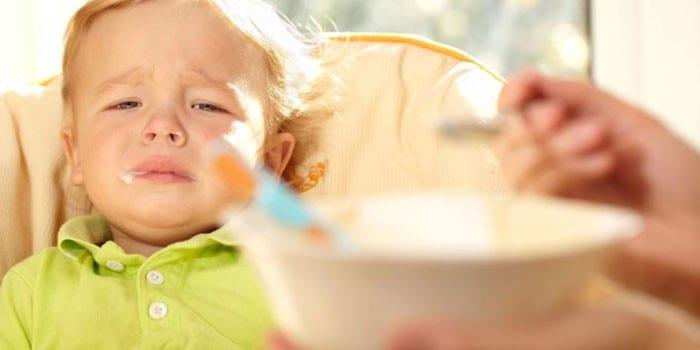 Ребенка кормят из ложечки