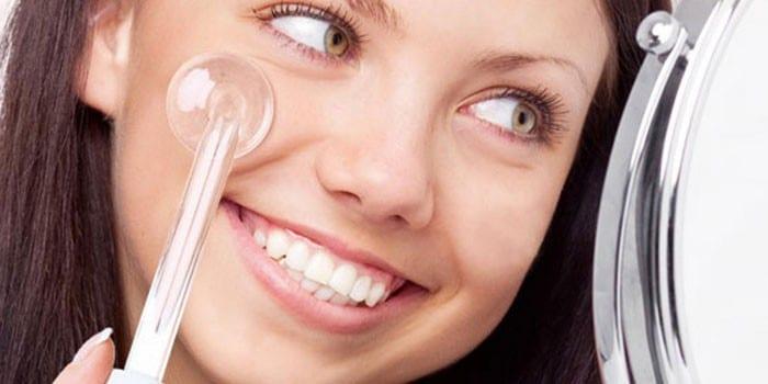 Девушка проводит процедуру дарсонвализации лица перед зеркалом