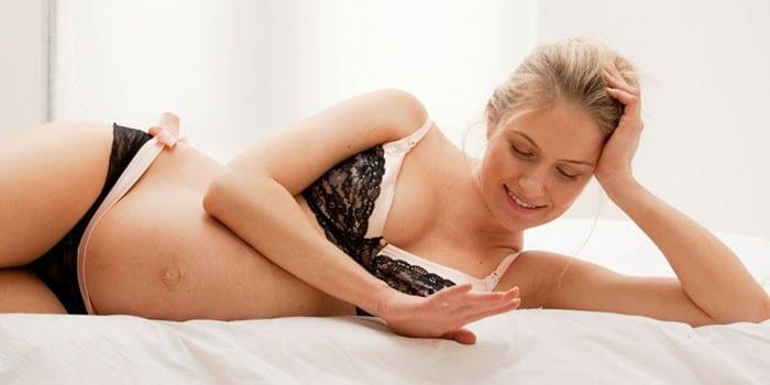 Беременная девушка в комплекте нижнего белья
