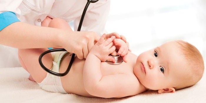 Врач слушает стетоскопом дыхание грудного ребенка