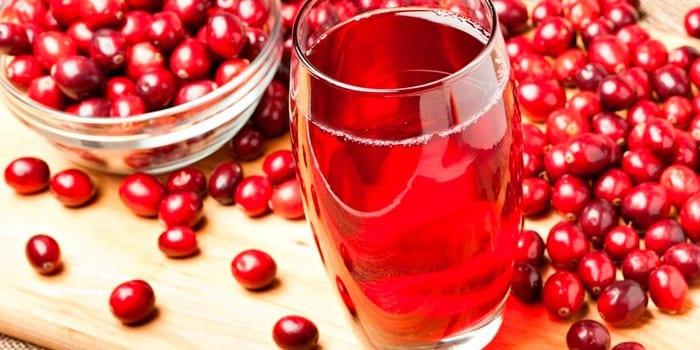 Клюквенный морс в стакане и свежие ягоды