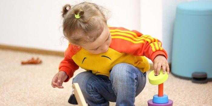 Девочка играет с пирамидкой