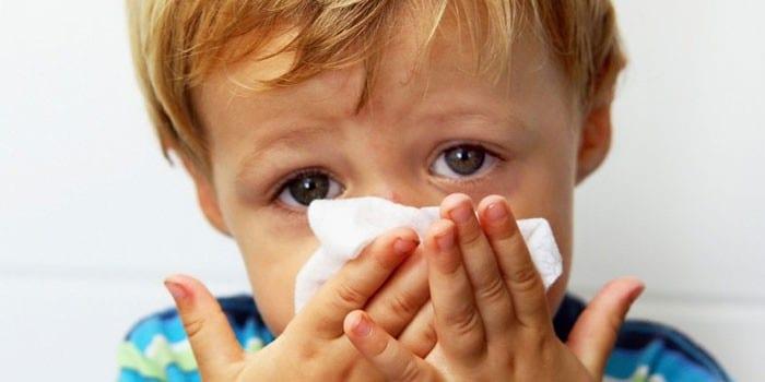 Ребенок закрывает нос платком