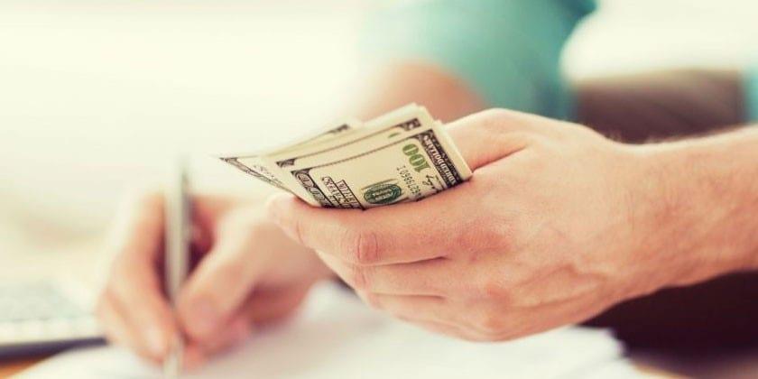 Человек держит деньги в руках и ведет запись