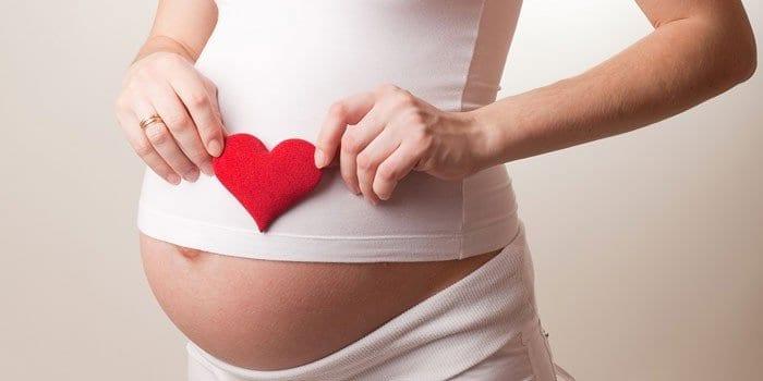 Беременная девушка с сердечком в руках