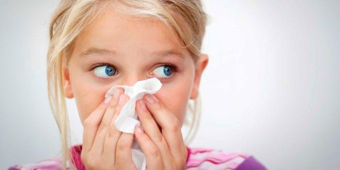 Девочка закрывает нос платком
