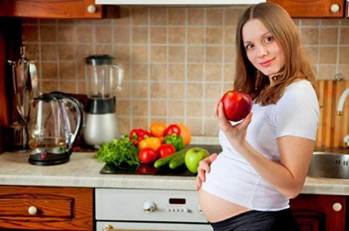 Беременная девушка с яблоком в руке