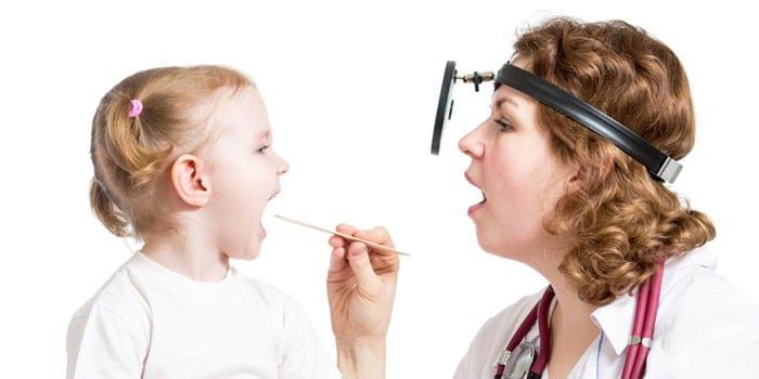 Отоларинголог осматривает горло девочки