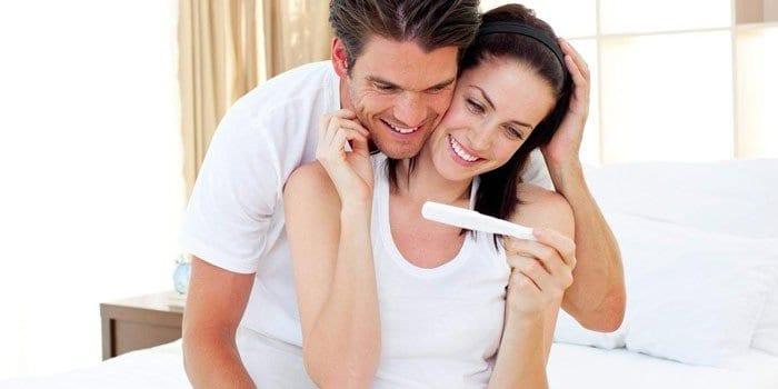 Мужчина и женщина смотрят на тест на беременность