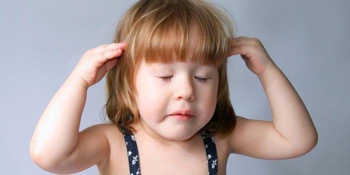 Девочка держится руками за голову