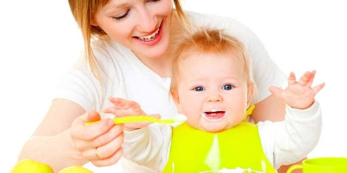 Женщина кормит малыша
