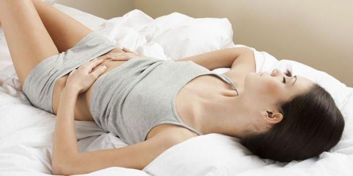 Девушка лежит на кровати и держит руки на животе