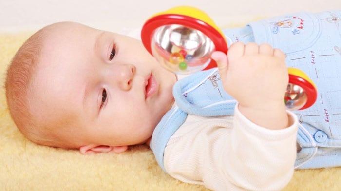 Ребенок 3 месяцев с погремушкой