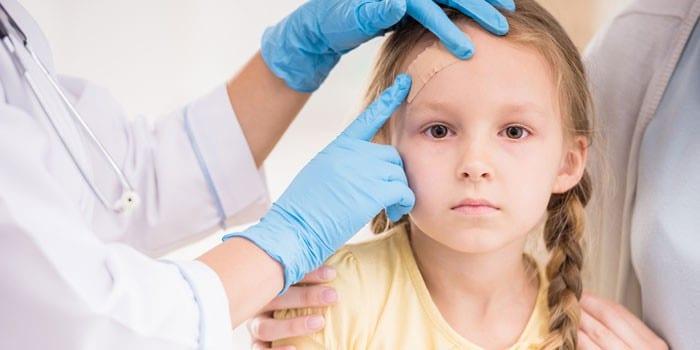 Медик наклеивает пластырь на лоб девочки