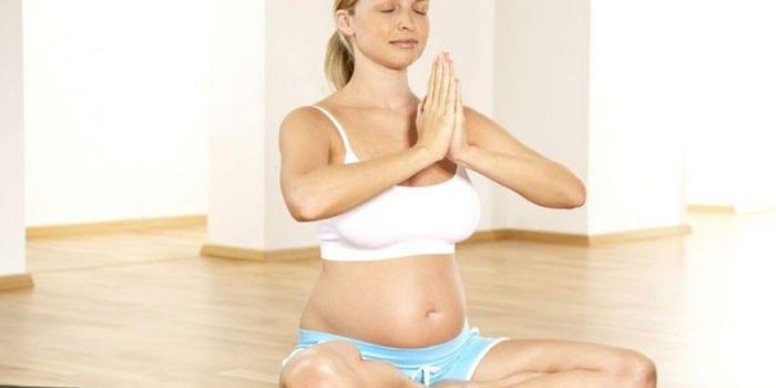 Беременная девушка занимается йогой