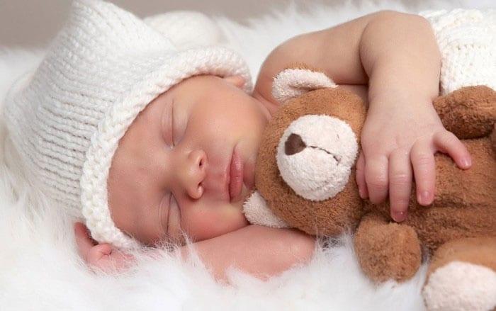 Новорожденный спит с мягкой игрушкой