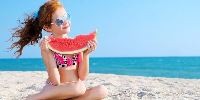 Девочка ест арбуз на пляже