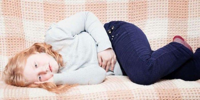 Девушка лежит на диване и держится рукой за живот