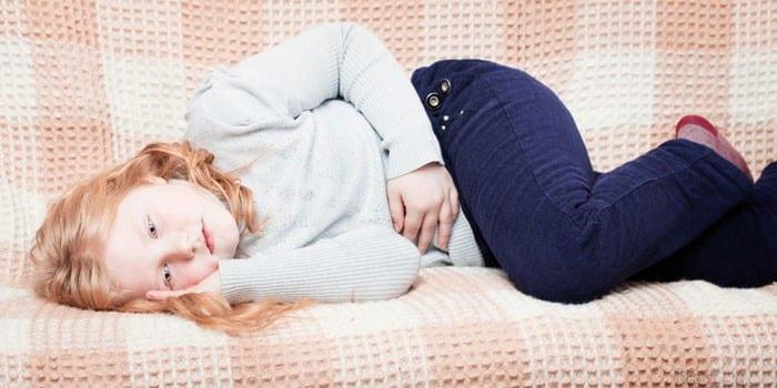 Девочка лежит на диване и держится рукой за живот