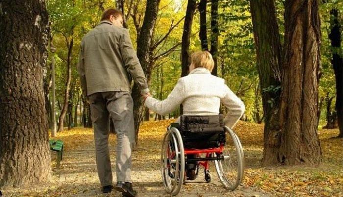 Мужчина держит за руку женщину в инвалидной коляске